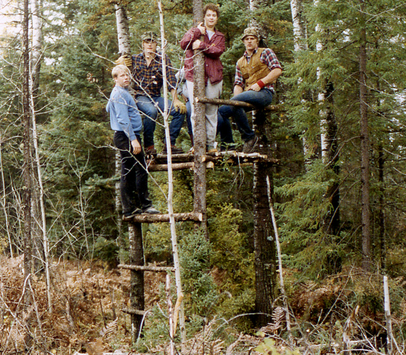 Color photgraph of a much larger, and higher platform tree stand. There are 4 hunters from the Nordberg Hunting Group hanging on it.